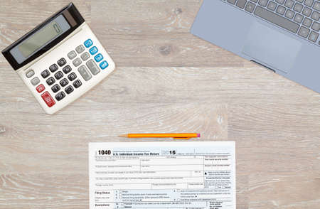 irs: USA IRS tax form 1040 for year 2015 with pencils and calculator with a laptop keyboard on wooden desk and taken from above