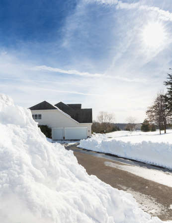 cleared: Piles of snow after the driveway to a modern single family house has been cleared after blizzard and snow drifts Stock Photo