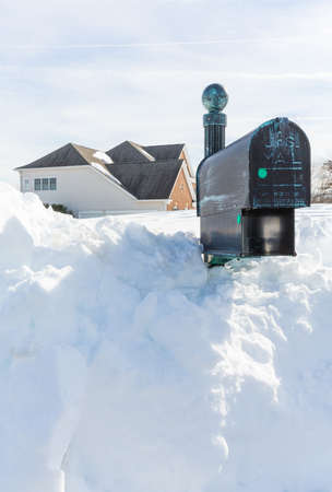 bury: Piles of snow bury the mail box of a modern single family house after blizzard and snow drifts Stock Photo