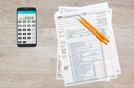 irs: USA IRS tax form 1040 for year 2015 with pencils and calculator app on smartphone on wooden desk and taken from above
