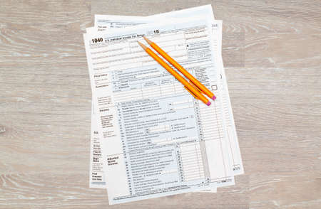 irs: USA IRS tax form 1040 for year 2015 with pencils on wooden desk and taken from above