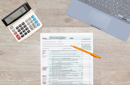 irs: USA IRS tax form 1040EZ for year 2015 with pencils and calculator with a laptop keyboard on wooden desk and taken from above