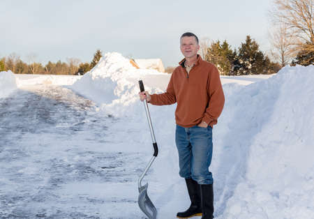snow drift: Senior man with snow shovel looking content after removing snow drifts on driveway by digging out from the blizzard