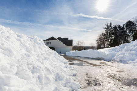 single family: Piles of snow after the driveway to a modern single family house has been cleared after blizzard and snow drifts Stock Photo