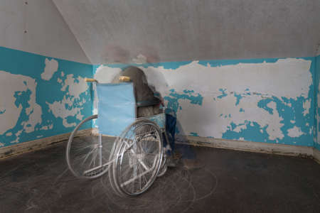 ghostly: Ghostly person in old wheelchair in motion blur and trapped in corner of a room Stock Photo