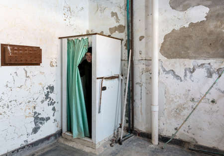 shower stall: Senior man emerges from shower stall and curtain inside Trans-Allegheny Lunatic Asylum in Weston, West Virginia, USA
