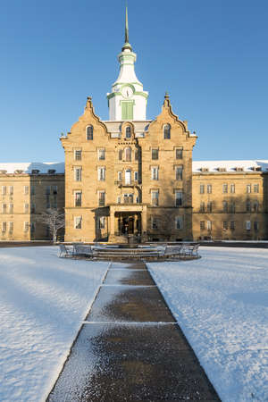 lunatic: Entrance and clock tower of Trans-Allegheny Lunatic Asylum which is a Kirkbride Psychiatric hospital  in Weston, West Virginia, USA