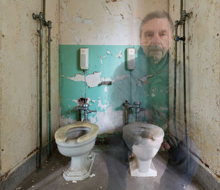 lunatic: Ghostly senior man sitting on toilet inside Trans-Allegheny Lunatic Asylum in Weston, West Virginia, USA