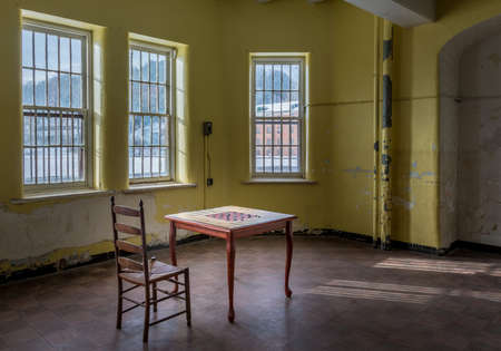 Single chair and game table inside Trans-Allegheny Lunatic Asylum in Weston, West Virginia, USA