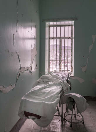 lunatic: Bed or stretcher inside empty room in Trans-Allegheny Lunatic Asylum in Weston, West Virginia, USA Stock Photo