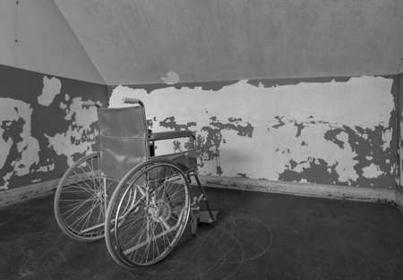 Old wheelchair facing the wall and trapped in corner of a room Stock fotó