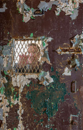 Ghostly senior man behind metal barred door leading to cell and holding onto the bars of the door photo
