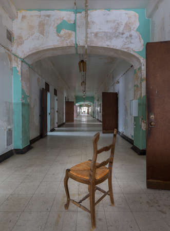 lunatic: Chair looking down long corridor inside Trans-Allegheny Lunatic Asylum in Weston, West Virginia, USA
