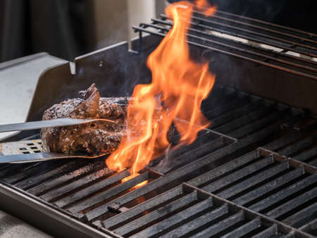 barbecuing: Close up of large piece of steak or beef flaming on barbeque