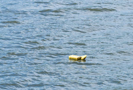 flotation: Yellow life preserver abandoned and floating down the river with nobody there