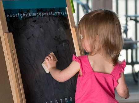 playtime: Young two year old girl cleaning a blackboard on an easel during playtime Stock Photo
