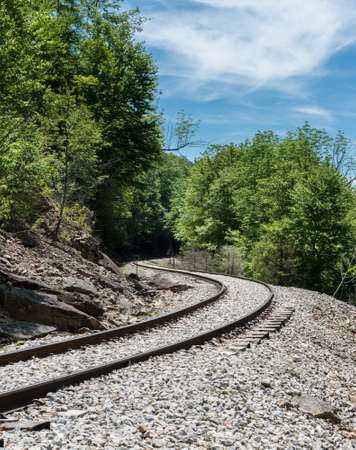 forest railroad: Durbin and Greenbrier Valley Railroad track winds through forest on the train trip from Elkins WV Stock Photo
