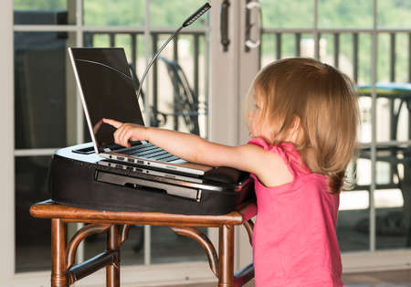 two year: Young two year old girl drawing with finger on laptop touchscreen on wooden table Stock Photo