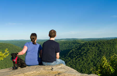 west virginia trees: Hikers look at Cheat River Canyon from Raven Rock in Coopers Rock State Forest West Virginia Stock Photo