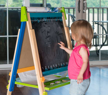playtime: Young two year old girl drawing with finger on blackboard on an easel during playtime