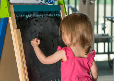 chalk drawing: Young two year old girl drawing with chalk on blackboard on an easel during playtime Stock Photo