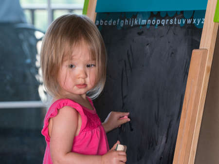 Young two year old girl drawing with chalk on blackboard and studying her subject