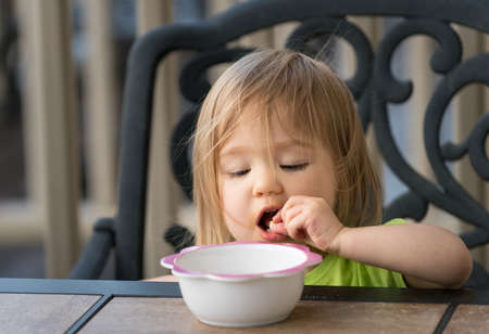 Small caucasian baby girl eating with fingers from bowl on outdoor table