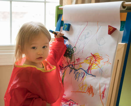playtime: Young two year old girl drawing with crayon on paper mounted on an easel during playtime