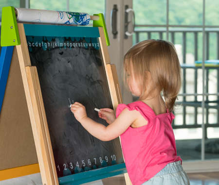 two year old: Young two year old girl drawing with chalk on blackboard and using both hands ambidextrously