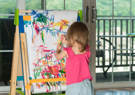 playtime: Young two year old girl drawing with pencil on paper mounted on an easel during playtime