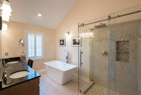 walk in: Interior of modern bathroom with standalone tub, walk in double tiled shower and granite vanity bar