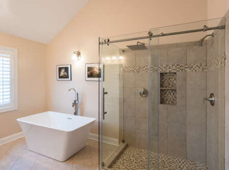 Interior of modern bathroom with standalone tub bath and walk in double tiled shower with rain head