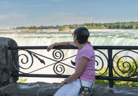 horseshoe falls: Senior woman looks at Canadian or Horseshoe waterfall from Canadian side of Niagara Falls Stock Photo
