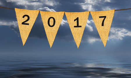 pessimistic: High resolution isolated sack cloth pennants with letters on each to create pennant flag message of New Years Eve 2017 in the  dark stormy sky giving pessimistic view Stock Photo