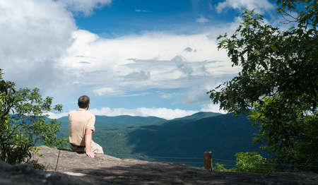 overlook: Senior man looking at view from the trail to the summit of Whiteside Mountain near Highlands and Cashiers in North Carolina