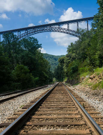 west river: Railway rails alongside river underneath the high arched New River Gorge bridge in West Virginia