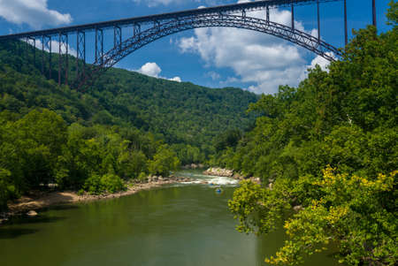 rafters: Rafters float towards the rapids under the high arched New River Gorge bridge in West Virginia Stock Photo