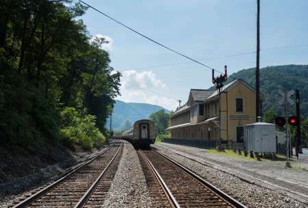 mainline: Amtrak train passes old station building in ghost town of Thurmond West Virginia are owned by the National Park Service Stock Photo