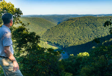 Senior adult hiker overlooks the Cheat River Canyon from Snake River Wildlife Management Area near Morgantown in West Virginia photo