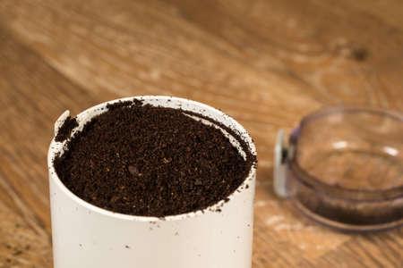 molinillo: Vista de macro de granos de café en molinillo eléctrico de pie en la mesa de cocina de madera vieja