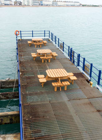 View across and empty deserted tables and benches at the end of the pier in Eastbourne looking towards the promenade Stock Photo
