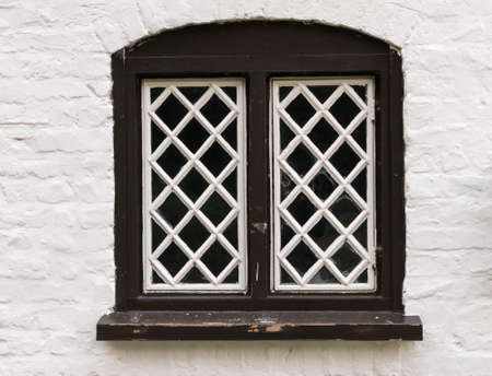 diamond shaped: Diamond shaped glass in wooden frame in old stone cottage painted in white.