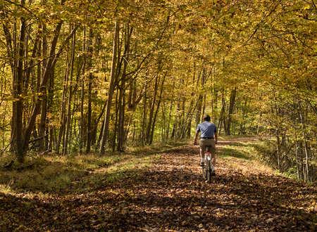 senior adult man: Senior adult caucasian man cycling away down a leaf covered Deckers Creek Rail trail near Morgantown in West Virginia Stock Photo