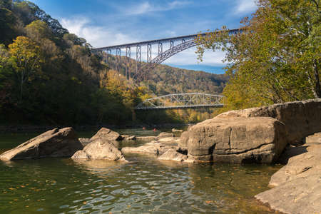 Kayakers float towards the rapids under the high arched New River Gorge bridge in West Virginia