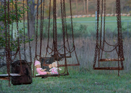 chain swing ride: Halloween image of an abandoned childs dolly and small soft toy of girl on old rusty swing at fun fair
