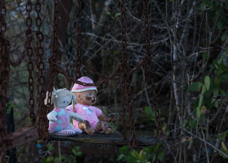 abandoned: Halloween image of an abandoned childs dolly and small soft toy of girl on old rusty swing at fun fair