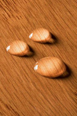 3 개의 둥근 물은 마루 또는 다른 경재의 닦은 나무 표면에 서있다 스톡 콘텐츠