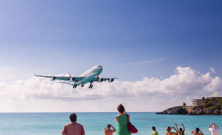 International jet flight lands over Maho beach at Princess Juliana airport on Caribbean island of St Martin