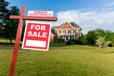 single family: For Sale and Under Contract  sign in front of large brick single family house in expansive grass yard for real estate opportunity Stock Photo