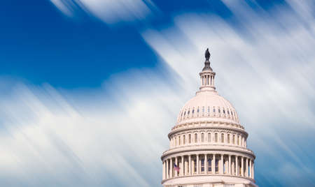 illustrating: Motion blur clouds illustrating time moving quickly past  dome of Capitol senate building in Washington DC
